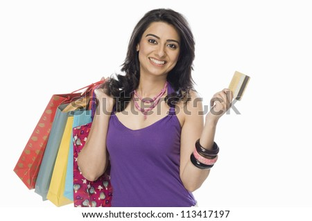 Portrait of a woman carrying shopping bags and showing a credit card