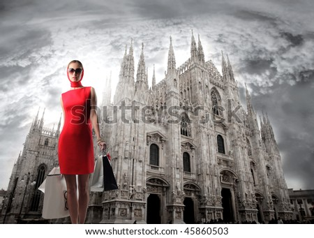 Portrait of a woman carrying some shopping bags in front of the Dome of Milan - stock photo