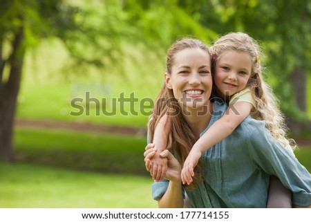 Portrait of a woman carrying young girl at the park - stock photo