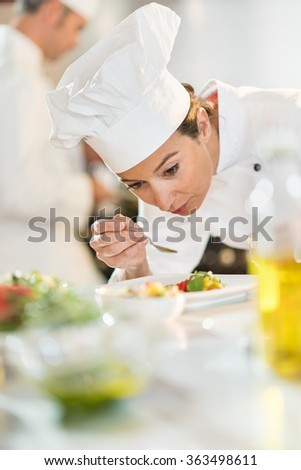 Portrait of a woman chef in her thirties. She is focused on the tasting of a colorful plateful She is wearing white chef clothes and hat. Another man chef is cooking in the blurred background. - stock photo