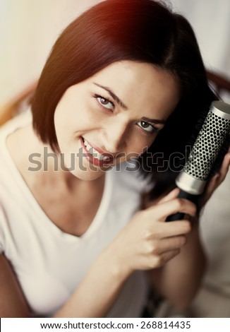 Portrait of a woman combing her hair - stock photo