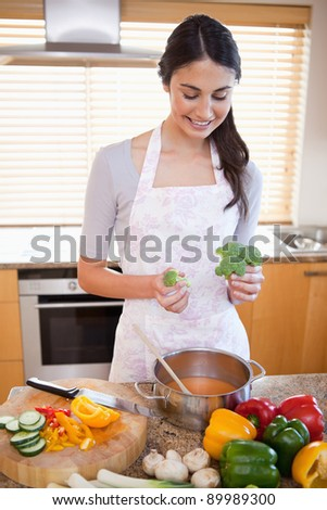 Portrait of a woman cooking a soup in her kitchen - stock photo