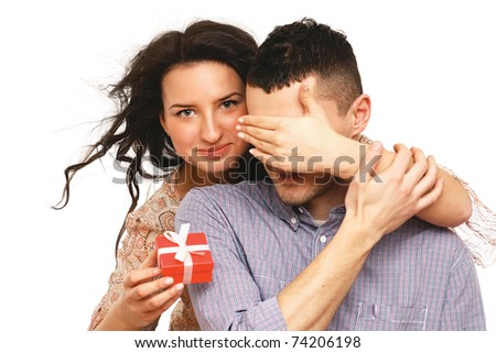 Portrait of a woman covering her boyfriend's eyes to surprise him with a gift - stock photo