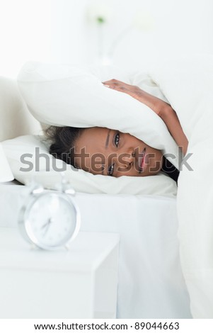 Portrait of a woman covering her ears while her alarm clock is ringing in her bedroom - stock photo
