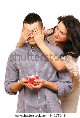 Portrait of a woman covering her husband's eyes to surprise him with a gift - stock photo