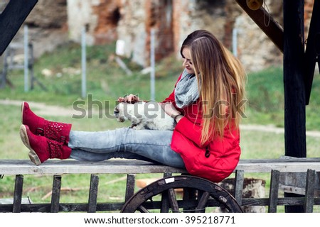 Portrait of a woman dressed in red with a white cat in her arms - stock photo