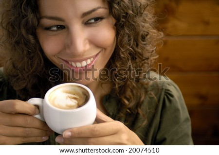 Portrait of a woman drinking cappuccino - stock photo