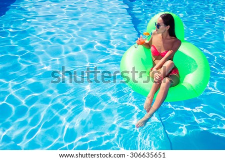 Portrait of a woman drinking cocktail on air mattress in swimming pool