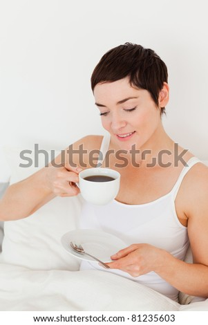 Portrait of a woman drinking coffee in her bedroom - stock photo