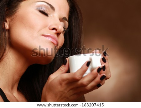 Portrait of a woman drinking coffee , isolated on beige background - stock photo