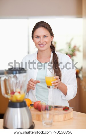Portrait of a woman drinking fresh fruits juice in her kitchen - stock photo