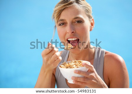 Portrait of a woman eating a bowl of cereals - stock photo