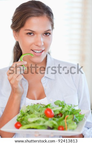 Portrait of a woman eating a salad in her kitchen