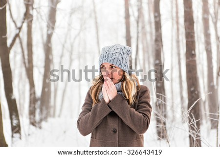 Portrait of a woman feeling cold in winter - stock photo
