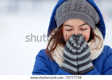 Portrait of a woman feeling cold in winter - outdoors - stock photo