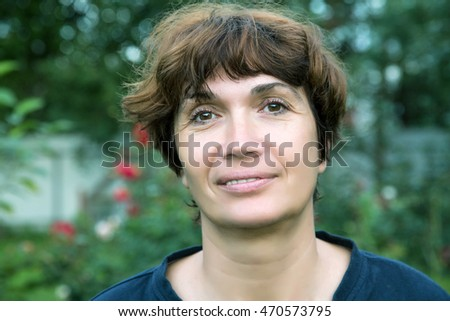 portrait of a woman fifty years against the backdrop of nature in the summer