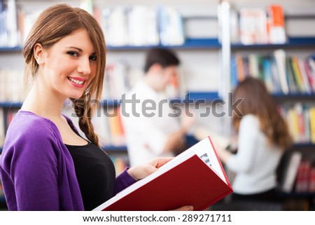 Portrait of a woman holding a book in a library - stock photo