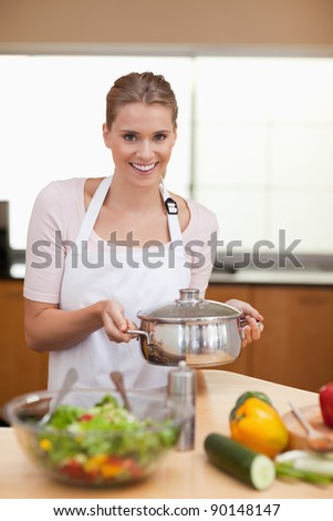 Portrait of a woman holding a sauce pan in her kitchen - stock photo