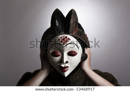 Portrait of a woman holding a traditional African mask. - stock photo