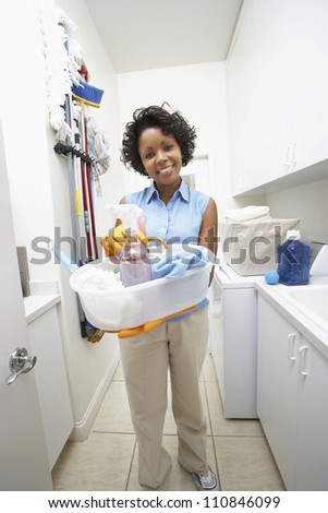 Portrait of a woman holding bucket of cleaning equipments - stock photo