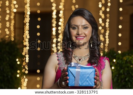 Portrait of a woman holding gift - stock photo