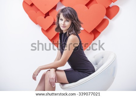 Portrait of a woman in a black bodycon dress in white modern chair with decorative hearts on the background - stock photo