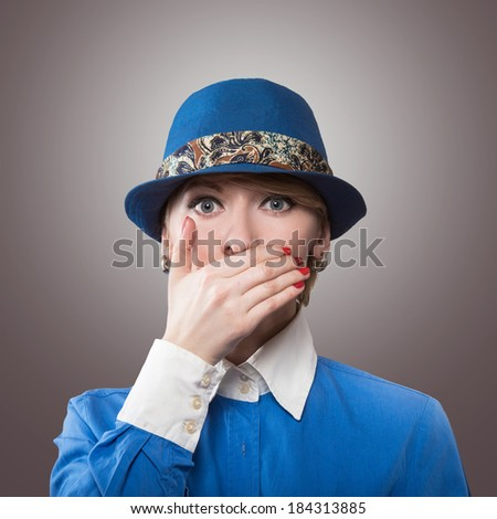 Portrait of a woman in a blue hat covering the mouth with her hand, gray background - stock photo