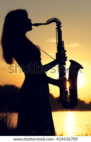 portrait of a woman in a dress playing the saxophone near the river
