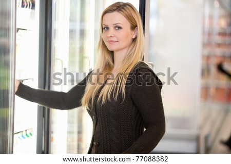 Portrait of a woman in a grocery store buying cold food - stock photo