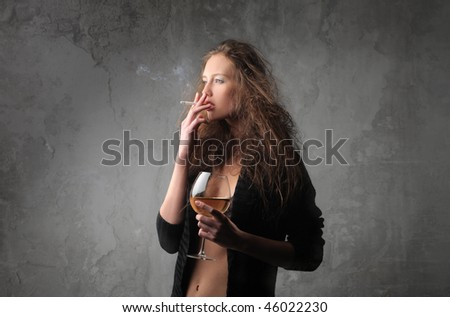Portrait of a woman in dressing gown smoking with a glass of liquor in her hand - stock photo