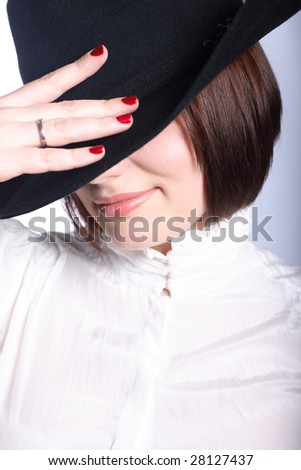 Portrait of a woman in hat closing her face - stock photo