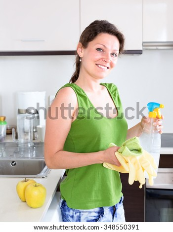 Portrait of a woman in kitchen holding a rag, rubber gloves and cleaning compound in a vaporizer