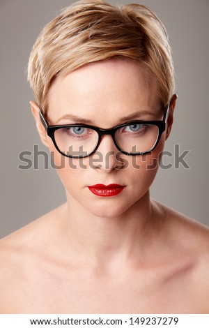 Portrait of a woman in modern glasses over grey isolated background