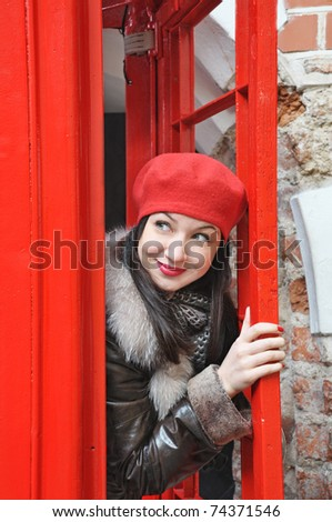 portrait of a woman in red hat look out from phonebox - stock photo