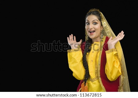 Portrait of a woman in yellow Punjabi dress with her mouth open - stock photo