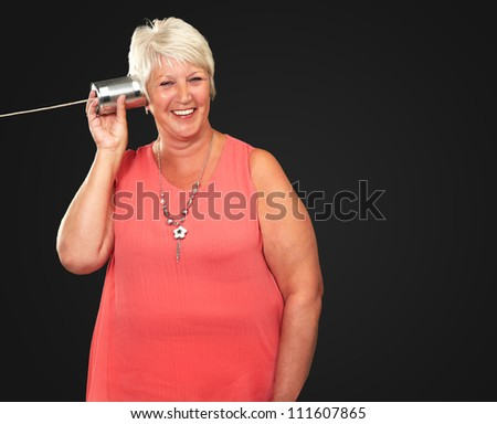 Portrait Of A Woman Listening To Tin Can Phone On A Black Background - stock photo