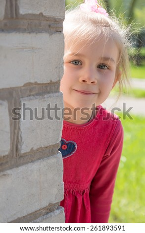 portrait of a woman looking around the corner. - stock photo