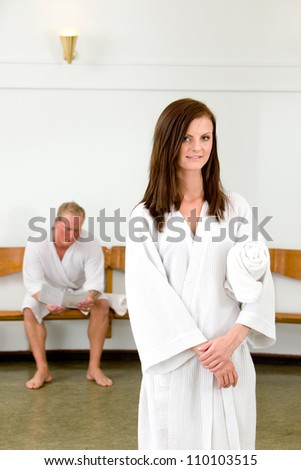 portrait of a woman looking at the camera in a wellness spa, with a man waiting in the background - stock photo