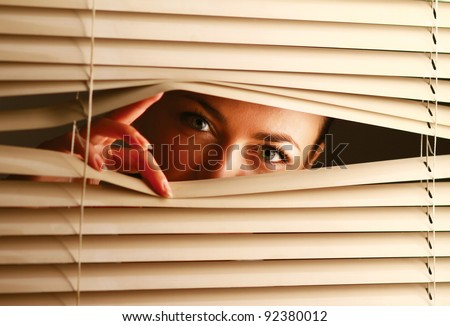 Portrait of a woman looking through out the blinds - stock photo