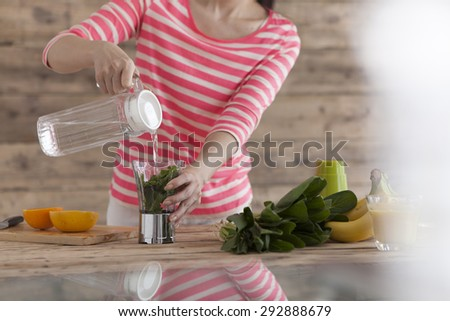 Portrait of a woman making a fresh juice in the kitchen - stock photo