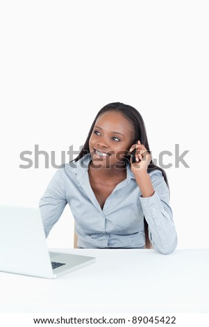 Portrait of a woman making a phone call while using a notebook against a white background - stock photo