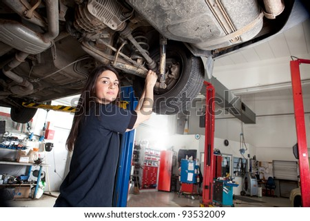 Portrait of a woman mechanic working on the underside of a car - stock photo