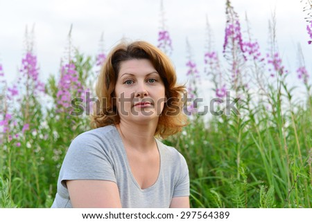 Portrait of a woman near willow-herb in the field