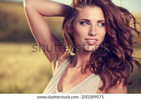 Chân dung của một người phụ nữ trên sân ngũ cốc vàng trong mùa hè
