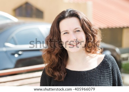 Portrait of a woman on the street in sunny weather.