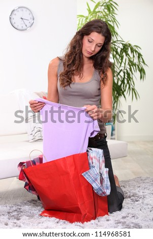 portrait of a woman opening shopping bag - stock photo
