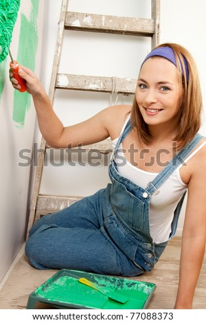 Portrait of a woman painting the wall green with a roller brush