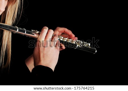Portrait of a woman playing transverse flute, isolated on black
