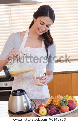 Portrait of a woman pouring fresh juice in a glass in her kitchen - stock photo