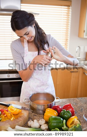 Portrait of a woman preparing a sauce in her kitchen - stock photo
